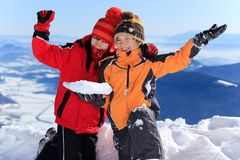 Children waving on mountaintop. Two happy children waving in snow on a sunny mountaintop Royalty Free Stock Photo