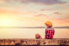 Children wear hat and red jacket sitting lonely on the ground. stock photos