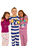 Children wearing pajamas with a freezing cold expression. Children wearing Christmas pajamas with a freezing cold facial and body expression Stock Images