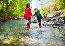 Children wearing rain boots jumping into a mountain river. Happy children wearing rain boots jumping into a mountain river stock photo