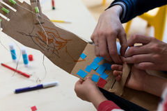 Children is wearing a robotic arm made with cardboard. Cardboard arm simulating robot is weared by a children helped by facilitator royalty free stock image