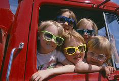 Children wearing sunglasses in red truck. Children wearing sunglasses in a red fire truck, Dairlyand, Wisconsin Royalty Free Stock Images