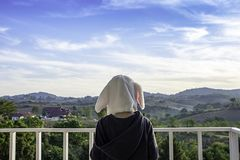 Children wearing winter coat and hat On the balcony overlooking the mountains and the sky.  stock images