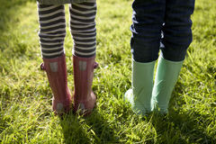 Children in wellington boots standing on grass Royalty Free Stock Photos