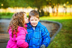 Children whispers in autumn park. Stock Photo