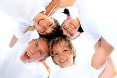 Children in white shirts. Four smiling sibling children in white shirts with their heads together as in a huddle stock image
