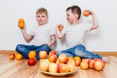 Children in white t-shirts and fruits on the floor. Little children in white t-shirts and fruits on the floor on white background stock photo