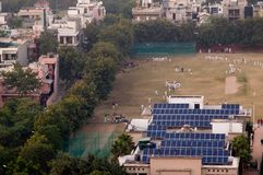 Children in white uniform playing on a cricket field powered by. Children in white cricket uniforms playing on a field powered by solar panels. Perfect example Stock Photos