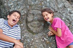 Children who imitate the expression of a face. Child imitating the expression of a face carved on the rock Stock Photos