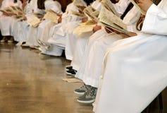 Children wihite white tunics of first communion at mass. In church royalty free stock image