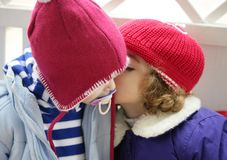 Children, winter red hat whispering in ear Stock Image