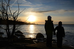 Children and winter sea sunset Stock Photos