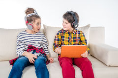 Children With Headphones And Digital Tablet Sitting On Sofa Royalty Free Stock Image