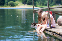 Children on a wooden pier. With the legs dipped into the pond Stock Images