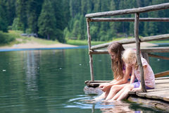 Children on a wooden pier. With the legs dipped into the pond Royalty Free Stock Image