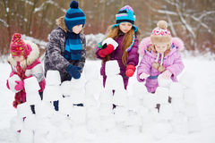 Children work at building wall from snow blocks Royalty Free Stock Photos