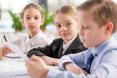 Children working with papers. Like adult business people Royalty Free Stock Images