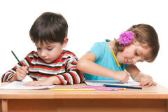 Children write at the desk. Little boy and little girl are sitting at the desk and write Stock Image