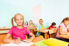 Children write in exercise books and sit at tables Stock Photos