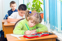 Children write at a lesson. In a class Royalty Free Stock Photo