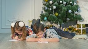 Children write letters to Santa Claus. To children it is cheerful. Little boy and girl lie on a floor near Christmas stock footage