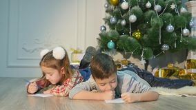 Children write letters to Santa Claus. To children it is cheerful. Little boy and girl lie on a floor near Christmas stock video footage