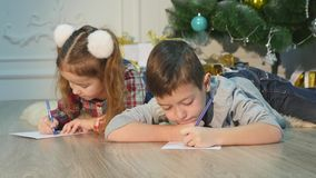 Children write letters to Santa Claus. To children it is cheerful. Little boy and girl lie on a floor near Christmas stock video