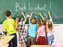 Children writing on blackboard. Stock Photo