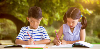 Composite image of children writing on books at table. Children writing on books at table against trees and meadow in the park Stock Image
