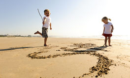 Children writing in sand Royalty Free Stock Images