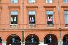 Children& x27 τα φορέματα μπαλέτου του s κρεμούν στα παράθυρα ενός κτηρίου τούβλου στην πόλη Στοκ φωτογραφίες με δικαίωμα ελεύθερης χρήσης