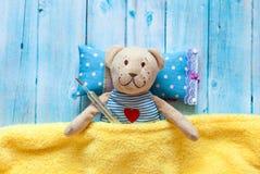 Children& x27; o urso de peluche macio do brinquedo de s na cama com termômetro e comprimidos, toma a temperatura de um vidro do  Fotos de Stock Royalty Free