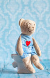 Children& x27 ; ours de nounours mol de jouet de s se reposant sur la toilette dans la maison de poupée Salle de bains bleue à Jo Photo stock