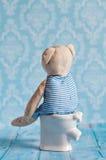 Children& x27 ; ours de nounours mol de jouet de s se reposant sur la toilette dans la maison de poupée Salle de bains bleue à Jo Photo libre de droits