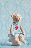 Children& x27 ; ours de nounours mol de jouet de s se reposant sur la toilette dans la maison de poupée Salle de bains bleue à Jo Photos libres de droits