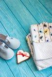 Children& x27; s-Kleidung, Schuhe und Lebkuchenherz Stockfoto