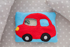 Children's soft toy red car of colored fleece for motor development. Bag  filled with plastic beads and figurines on a Stock Images