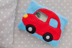 Children's soft toy red car of colored fleece for motor development. Bag  filled with plastic beads and figurines on a Royalty Free Stock Photos