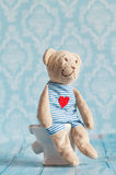 Children's soft toy teddy bear  sitting on the toilet in the doll house. Blue bathroom to . Playing with dolls in the Royalty Free Stock Photos