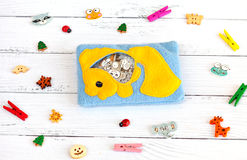 Children's toys made of colored fleece for motor development. Bag with yellow fish filled plastic beads and figurines Royalty Free Stock Image