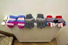 Children& x27;s warm hand knitted striped woolen gloves drying on hea