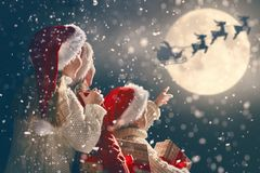 Children with xmas presents. Merry Christmas and happy holidays! Cute little children with xmas presents. Santa Claus flying in his sleigh against moon sky. Kids stock photos