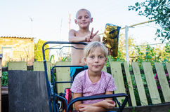 Children in the yard of the rural house, brother sister does horns Royalty Free Stock Images