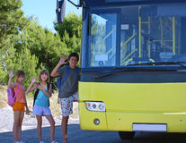 Children and yellow school bus. Back to school. Image of a young boy and girls (best friends) sent greetings to his family and enter into a yellow school bus stock photography