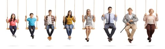 Children, young people and seniors sitting om swings and smiling. Full length portrait of a children, young people and seniors sitting om swings and smiling stock images