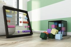 Children s abacus and colored building blocks. Childrens abacus with colorful beads and a building blocks container standing on the wooden floor of a green and Stock Photography