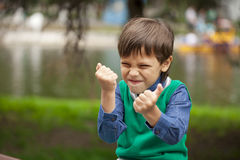 Childrens aggression. Portrait of little boy outdoor at the summer day Stock Image