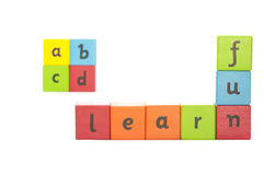 Childrens Alphabet Blocks. Painted wooden blocks with letters on  them used for early learning spelling out the words learn and fun with abcd out of focus in Royalty Free Stock Images