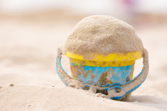 Childrens bucket with sand on beach Royalty Free Stock Images