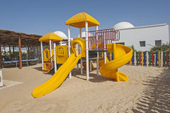 Childrens climbing frame and slide in tropical resort playground Royalty Free Stock Images